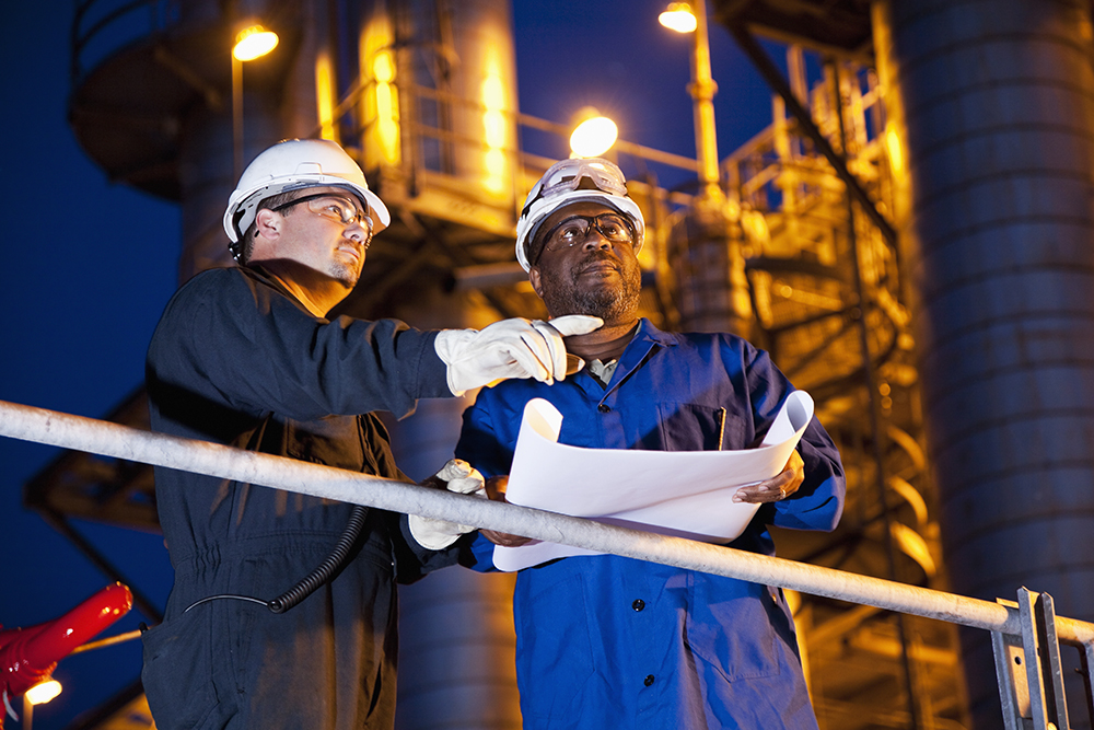 two men collaborating while performing a refinery inspection